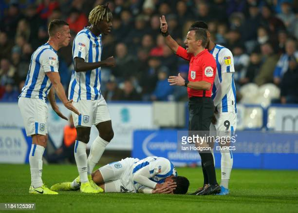 Huddersfield Town's Christopher Schindler lis on the pitch with an injury as referee Keith Stroud calls for physio Huddersfield Town v Birmingham...