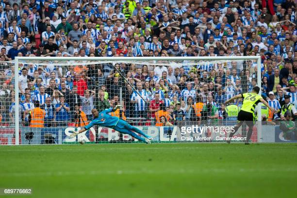 Huddersfield Town's Christopher Schindler scores the winning penalty past Reading's Ali AlHabsi in the penalty shootout during the EFL Sky Bet...