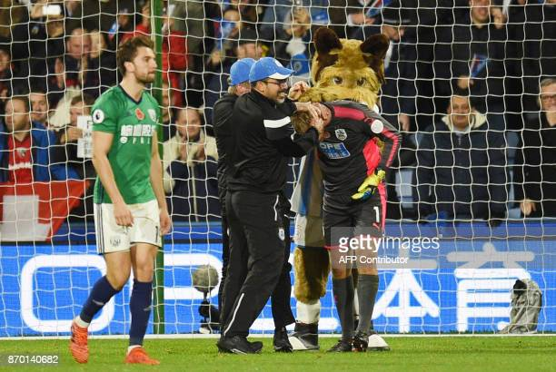Huddersfield Town's Danish goalkeeper Jonas Lossl celebrates with Huddersfield Town's German head coach David Wagner after winning the English...