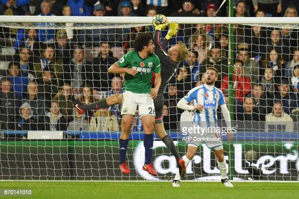 Huddersfield Town's Danish goalkeeper Jonas Lossl makes a save from West Bromwich Albion's Egyptian defender Ahmed Hegazy during the English Premier...