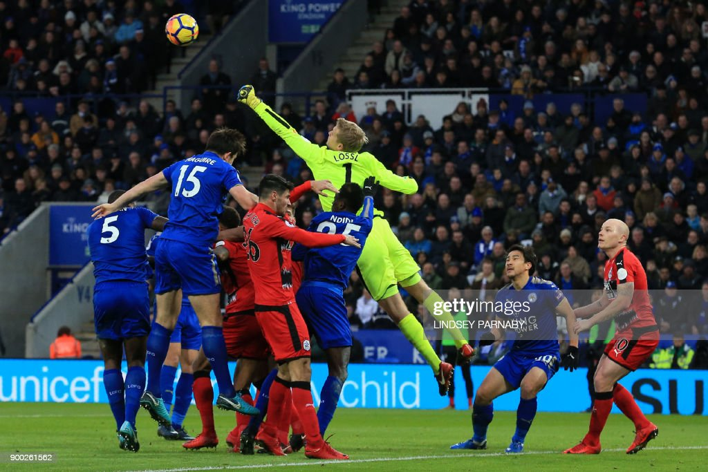 TOPSHOT - Huddersfield Town's Danish goalkeeper Jonas Lossl (C) punches the ball clear during the English Premier League football match between Leicester City and Huddersfield Town at King Power Stadium in Leicester, central England on January 1, 2018. / AFP PHOTO / Lindsey PARNABY / RESTRICTED TO EDITORIAL USE. No use with unauthorized audio, video, data, fixture lists, club/league logos or 'live' services. Online in-match use limited to 75 images, no video emulation. No use in betting, games or single club/league/player publications. /
