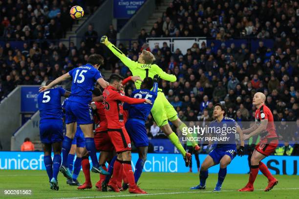 TOPSHOT Huddersfield Town's Danish goalkeeper Jonas Lossl punches the ball clear during the English Premier League football match between Leicester...