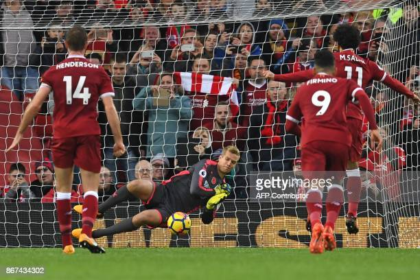 Huddersfield Town's Danish goalkeeper Jonas Lossl saves a penalty from Liverpool's Egyptian midfielder Mohamed Salah during the English Premier...