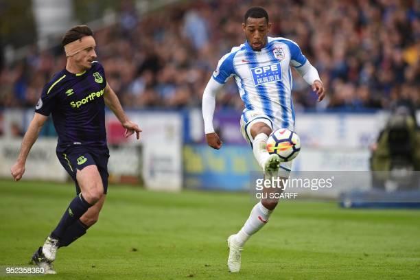 Huddersfield Town's Dutch midfielder Rajiv van La Parra vies with Everton's English defender Leighton Baines during the English Premier League...