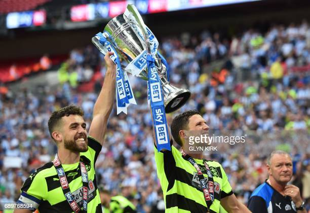 Huddersfield Town's English defender Tommy Smith and Huddersfield Town's English defender Mark Hudson hold up the Championship Playoff trophy as...