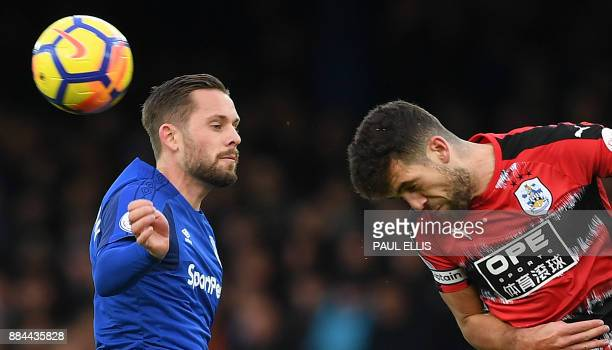 Huddersfield Town's English defender Tommy Smith heads the ball away from Everton's Icelandic midfielder Gylfi Sigurdsson during the English Premier...