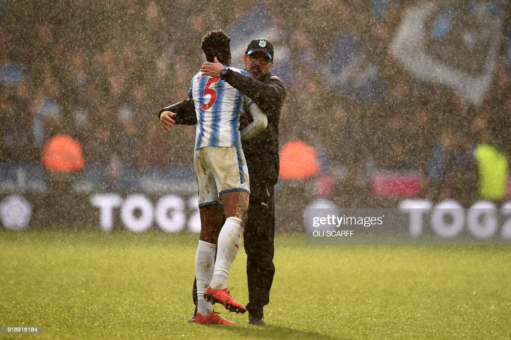 Huddersfield Town's German head coach David Wagner (R) celebrates victory with Huddersfield Town's Swiss-born Dutch defender Terence Kongolouring the English Premier League football match between Huddersfield Town and Bournemouth at the John Smith's stadium in Huddersfield, northern England on February 11, 2018. / AFP PHOTO / Oli SCARFF / RESTRICTED TO EDITORIAL USE. No use with unauthorized audio, video, data, fixture lists, club/league logos or 'live' services. Online in-match use limited to 75 images, no video emulation. No use in betting, games or single club/league/player publications. /