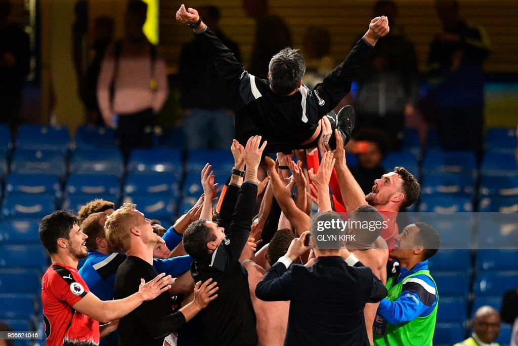 Huddersfield Town's German head coach David Wagner is thrown in the air by his players and staff as they celebrate after the final whistle during the English Premier League football match between Chelsea and Huddersfield Town at Stamford Bridge in London on May 9, 2018. - Huddersfield secured their Premier League survival with a 1-1 draw at Stamford Bridge on Wednesday. (Photo by Glyn KIRK / AFP) / RESTRICTED TO EDITORIAL USE. No use with unauthorized audio, video, data, fixture lists, club/league logos or 'live' services. Online in-match use limited to 75 images, no video emulation. No use in betting, games or single club/league/player publications. /