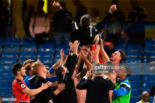Huddersfield Town's German head coach David Wagner is thrown in the air by his players and staff as they celebrate after the final whistle during the...