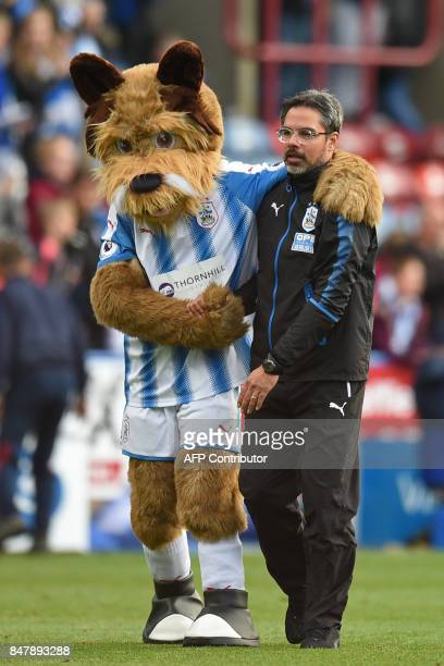 Huddersfield Town's German head coach David Wagner shares a moment with mascot Terry the Terrier on the pitch after the English Premier League...