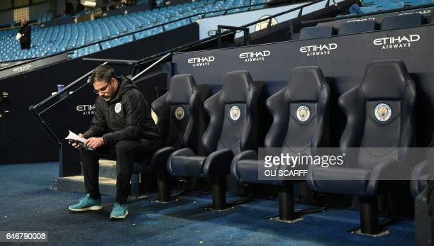 Huddersfield Town's German head coach David Wagner sits in the dugout ahead of the FA Cup fifth round replay football match between Manchester City...