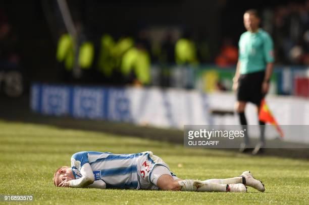 Huddersfield Town's Swiss defender Florent Hadergjonaj lies injured during the English Premier League football match between Huddersfield Town and...