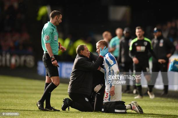 Huddersfield Town's Swiss defender Florent Hadergjonaj receives medical attention during the English Premier League football match between...