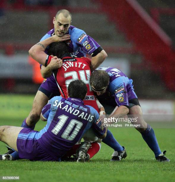 Huddersfield's Andy Raleigh and John Skandalis bring down Salford's Lee Jewitt during the Carnegie Challenge Cup Fifth Round match at The Willows...
