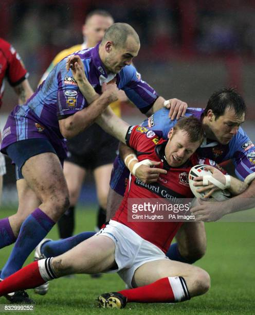 Huddersfield's Andy Raleigh and John Skandalis bring down Salford's David Hodgson during the Carnegie Challenge Cup Fifth Round match at The Willows...