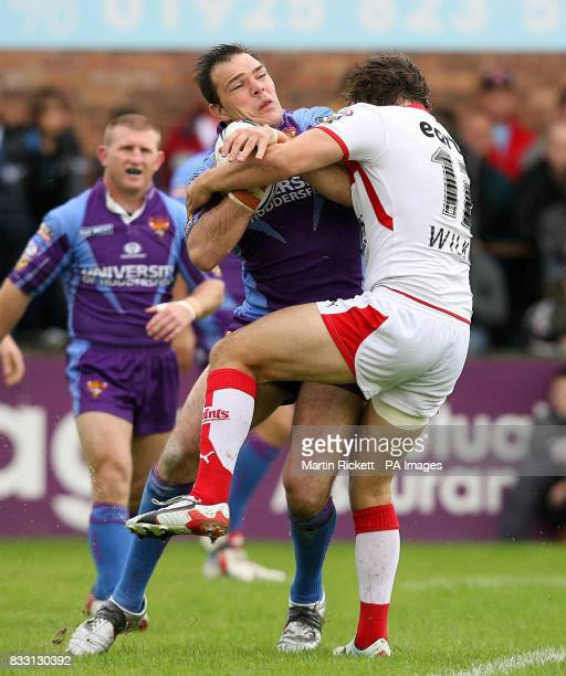 Huddersfield's John Skandalis is tackled by St Helens' Jon Wilkin during the engage Super League match at Knowsley Road St Helens