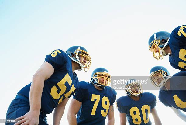 huddle of pro american football team against clear sky - safety american football player stock pictures, royalty-free photos & images