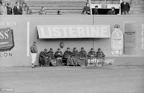 Huddled under blankets and an awning advertising Listerine brand mouthwash the New York Mets watch the on field action during their first year at the...