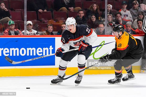 Hudson Fasching of Team United States carries the puck with Janik Moser of Team Germany following behind during the 2015 IIHF World Junior Hockey...