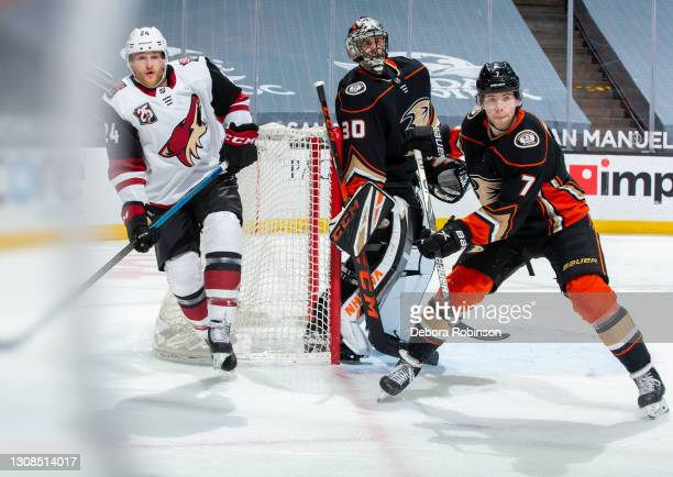 Hudson Fasching of the Arizona Coyotes and goaltender Ryan Miller and Ben Hutton watch play during the first period of the game at Honda Center on...