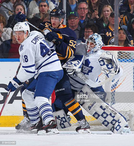 Hudson Fasching of the Buffalo Sabres battles for position against Andrew Campbell and Garret Sparks of the Toronto Maple Leafs during an NHL game on...