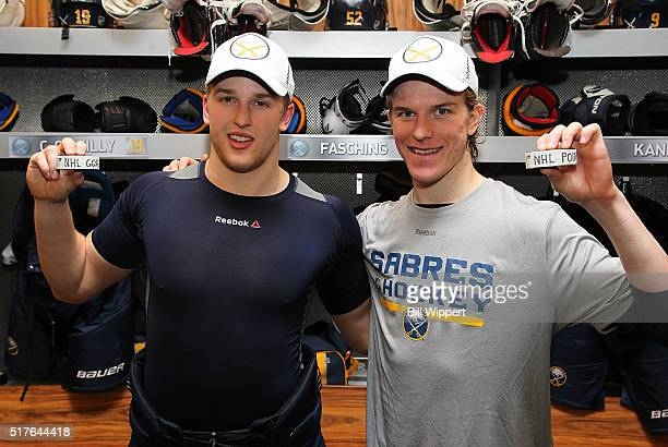 Hudson Fasching of the Buffalo Sabres holds the puck from his first NHL goal alongside Casey Nelson holding the puck from his first NHL point playing...