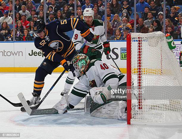Hudson Fasching of the Buffalo Sabres is defended by Devan Dubnyk and Nate Prosser of the Minnesota Wild during an NHL game at the KeyBank Center on...