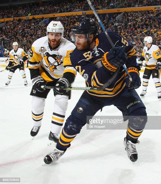 Hudson Fasching of the Buffalo Sabres is defended by Ian Cole of the Pittsburgh Penguins during an NHL game at the KeyBank Center on March 21 2017 in...
