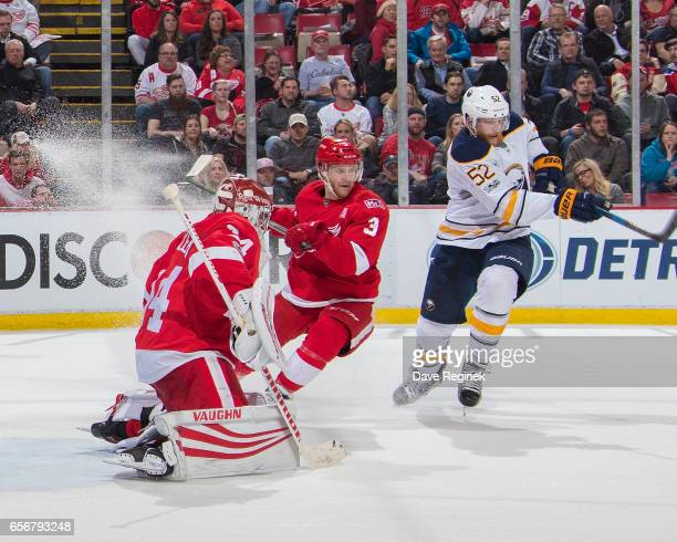Hudson Fasching of the Buffalo Sabres trees to deflect a shot past Petr Mrazek and Nick Jensen of the Detroit Red Wings during an NHL game at Joe...