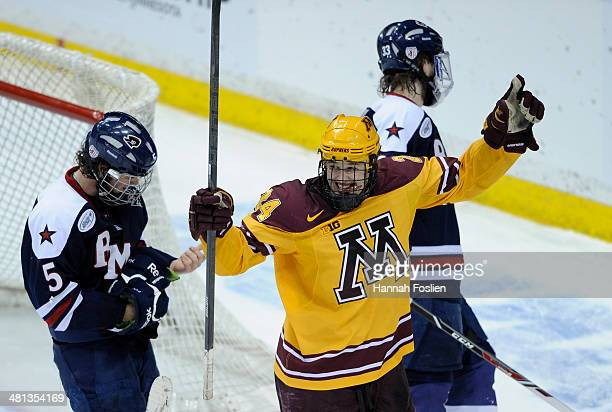 Hudson Fasching of the Minnesota Golden Gophers celebrates a goal as Evan Moore and Andrew Blazek of the Robert Morris Colonials look on during the...
