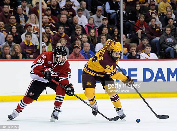 Hudson Fasching of the Minnesota Golden Gophers controls the puck against Andrew Prochno of the St Cloud State Huskies during the first period of the...