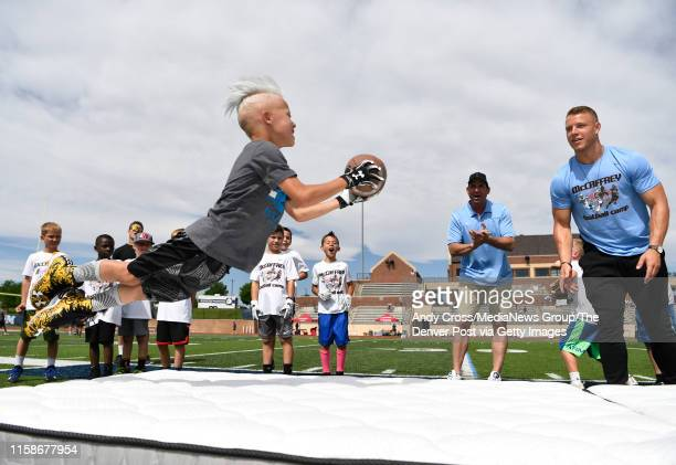 Hudson Larose launches in the air to catch the football tossed by Carolina Panthers RB Christian McCaffrey during the McCaffrey Football Camp at...
