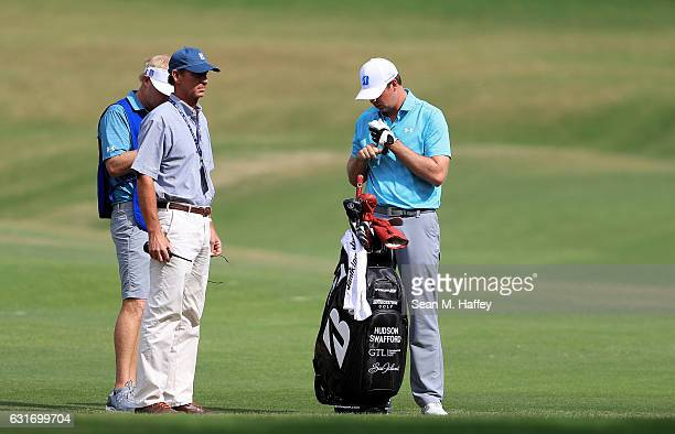 Hudson Swafford of the United States prepares to take a drop as PGA Tour Rules Official Robby Ware looks on during the third round of the Sony Open...