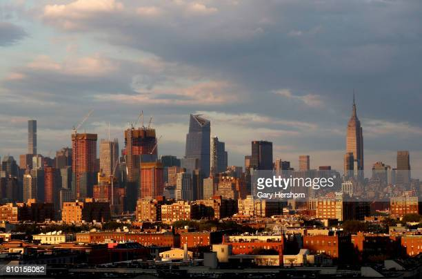 Hudson Yards development project and the Empire State Building in New York City rise above Hoboken NJ at sunset on July 4 2017 as seen from Union...