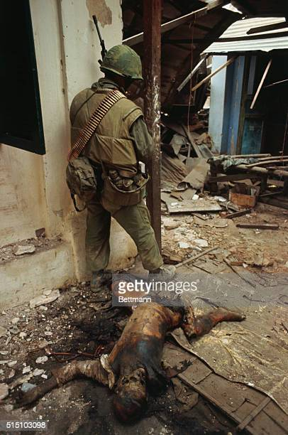 The charred remains of a Viet Cong soldier lie amid rubble in street where a US Marine stands on the alert for further confrontations with Communist...