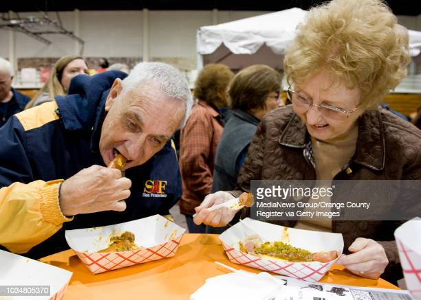 Huell Howser fans Eric Scandrett left of Santa Ana and Carol Howansky of Villa Park sample hot dogs from Pinks in the Hutton Sports Center at Chapman...
