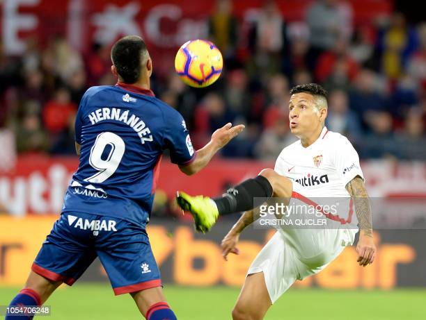 SD Huesca's Colombian forward Cucho Hernandez fights for the ball with Sevilla's Brazilian defender Guilherme Arana during the Spanish league...