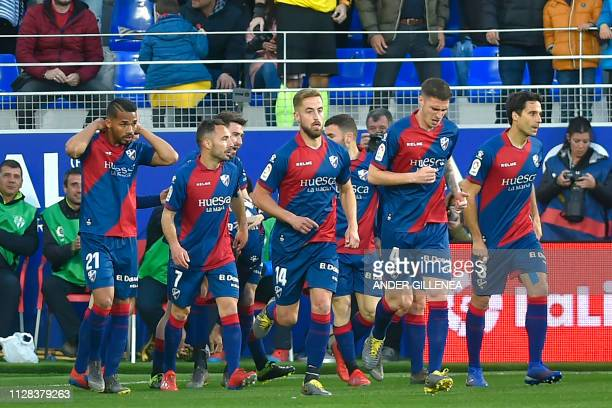 Huesca's players celebrate after scoring a goal during the Spanish league football match between SD Huesca and Sevilla FC at the El Alcoraz stadium...