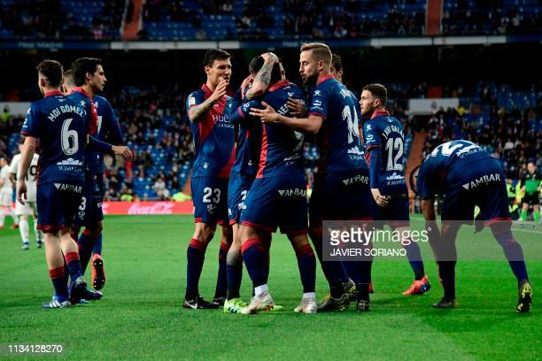 Huesca's players celebrate after scoring a goal during the Spanish League football match between Real Madrid CF and SD Huesca at the Santiago...