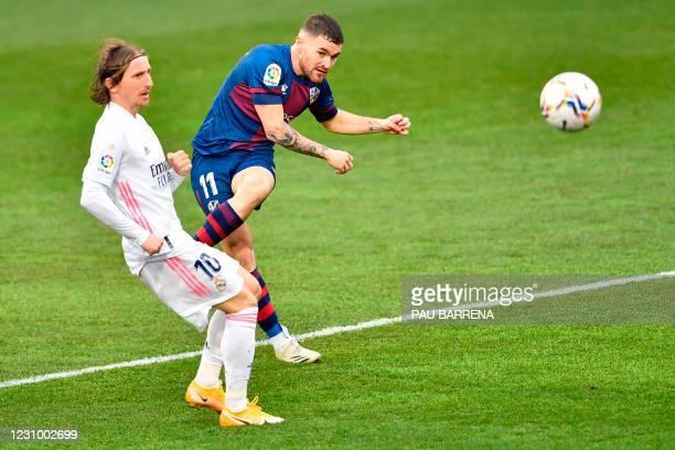 Huesca's Spanish defender Javi Galan scores a goal past Real Madrid's Croatian midfielder Luka Modric during the Spanish league football match...