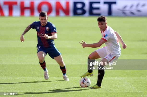 Huesca´s Spanish defender Javi Galan vies with Sevilla's Spanish midfielder Olivier Torres during the Spanish league football match between Sevilla...