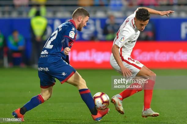 Huesca's Spanish defender Javier Galan challenges Sevilla's Spanish midfielder Jesus Navas during the Spanish league football match between SD Huesca...