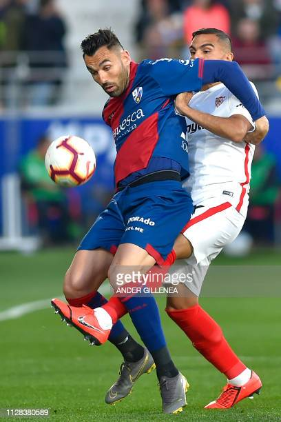SD Huesca's Spanish forward Enric Gallego challenges Sevilla's Argentinian defender Gabriel Mercado during the Spanish league football match between...