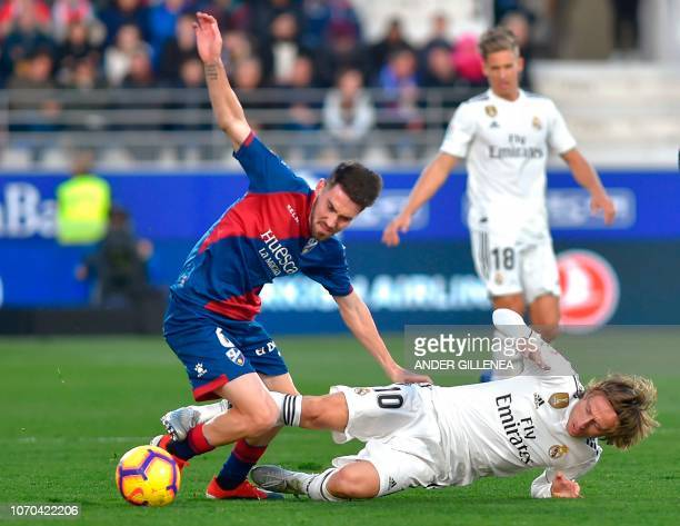 Huesca's Spanish midfielder Moises Gomez vies for the ball with Real Madrid's Croatian midfielder Luka Modric during the Spanish league football...