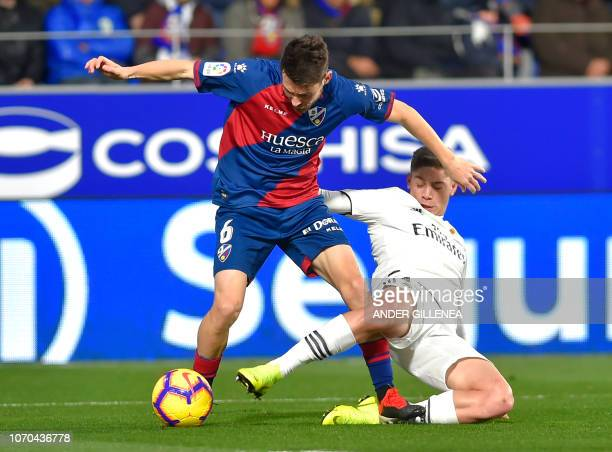 Huescas Spanish midfielder Moises Gomez vies with Real Madrid's Uruguayan midfielder Federico Valverde during the Spanish league football match...