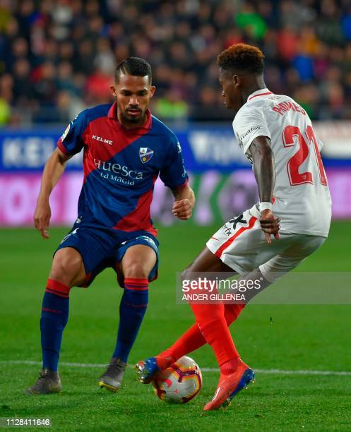 SD Huesca's Venezuelan midfielder Yangel Herrera challenges Sevilla's Dutch midfielder Quincy Promes during the Spanish league football match between...