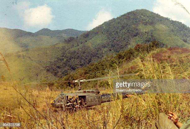 Huey helicopter landing in a field in Vietnam during the Vietnam War Marines disembarking from the helicopter the leg and hand of an American soldier...