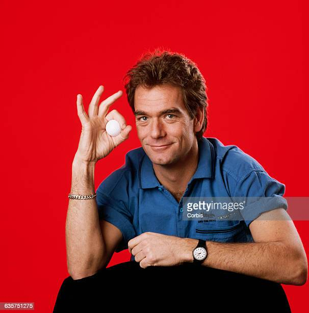 Huey Lewis holds a golf ball in an OK hand gesture He wears a blue shirt in front of a red backdrop