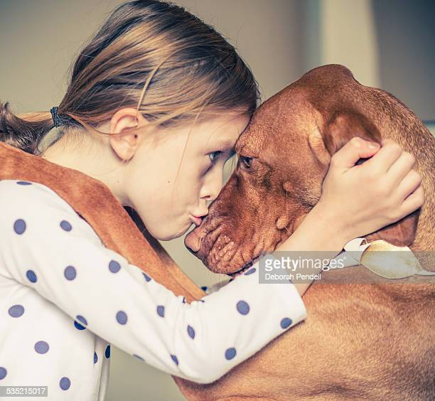 a hug between a young girl and her pet dog - animaux domestiques photos et images de collection