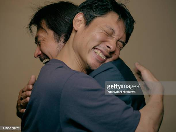 hug of joy - genderblend stock pictures, royalty-free photos & images